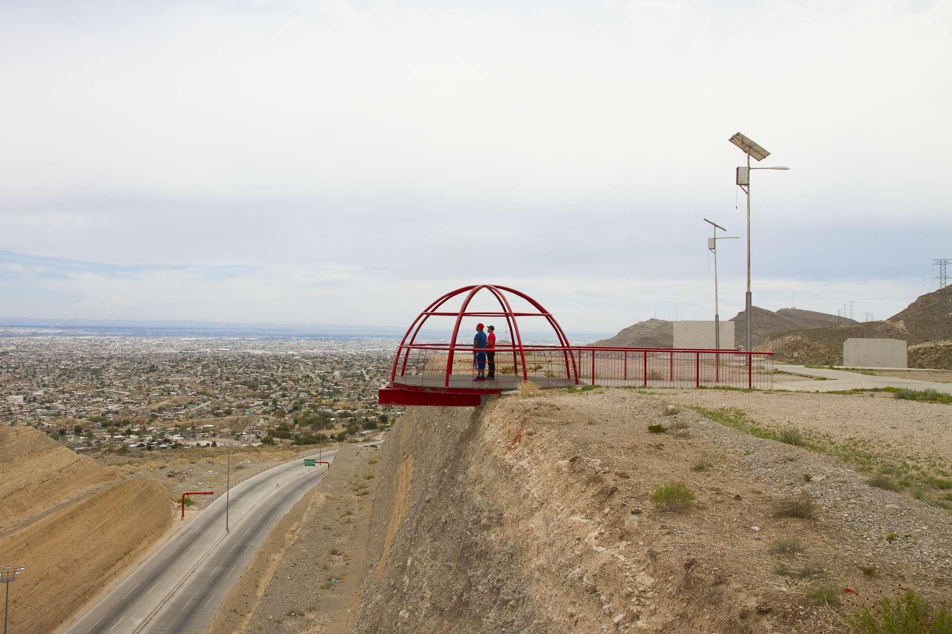 Deux hommes perchés sur un promontoir rouge, en train de regarder une ville au loin
